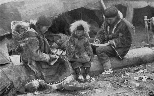 Família de esquimós usando Parka. A mãe usa uma com a bolsa de bebê.
