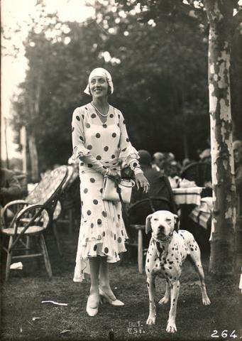 Mulher em evento social nos anos 30 usando vestido da ultima moda com estampa de Bolinhas.